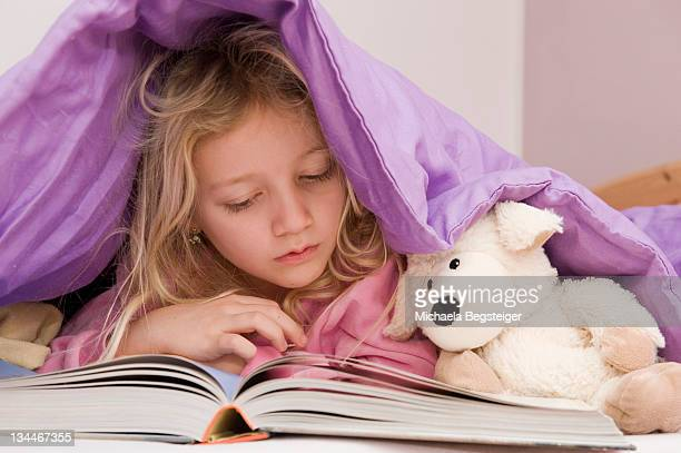 Girl lying under bedspread reading a book