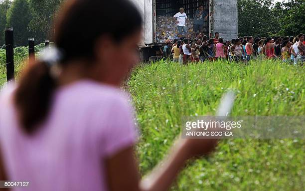 A girl makes a cell phone call as she queues at the entrance of the farm of Tailandia's mayor to receive a basket of basic food on February 28 2008...