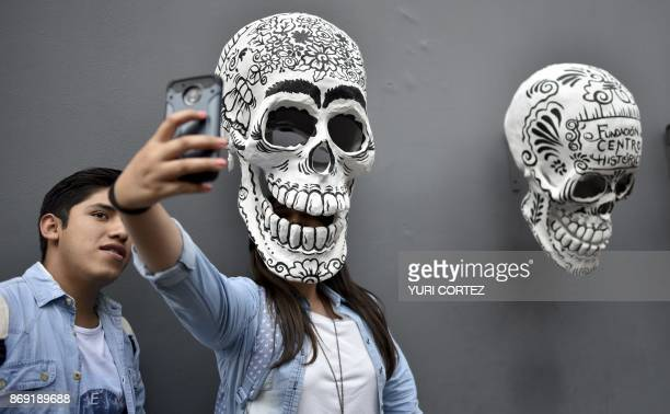 A girl makes a selfie with a skull during an exhibition and contest of offerings promoted by the Historic Center Foundation on the eve of the Day of...