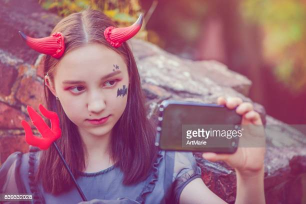 girl makes selfie at halloween - devil costume stock photos and pictures