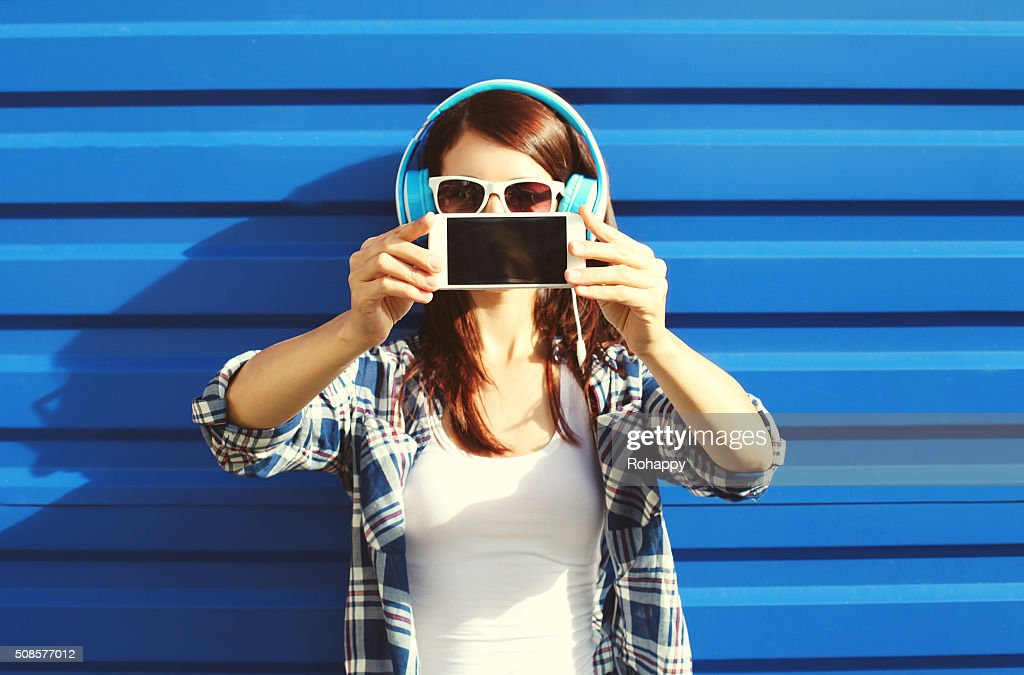 Girl makes self-portrait on smartphone listens music, screen phone : Stock Photo