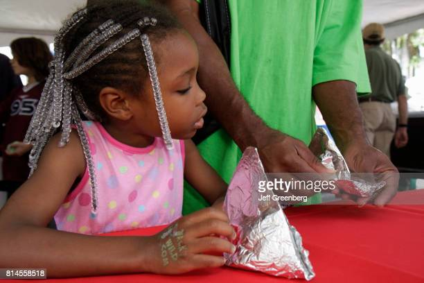 Girl making a hat out of aluminum paper at the Miami Goin' Green event.