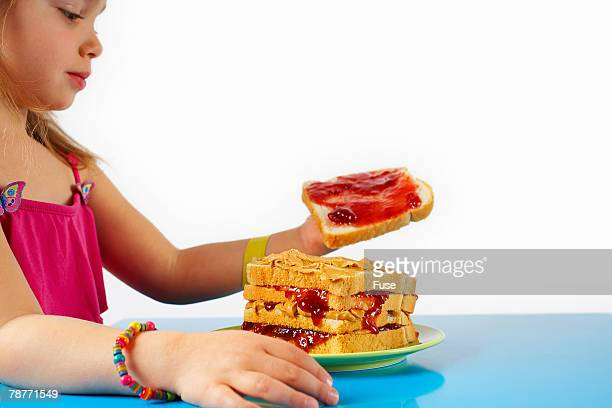 Girl Making a Large Peanut Butter and Jelly Sandwich