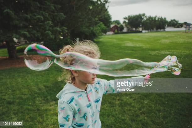 Girl making a long bubble