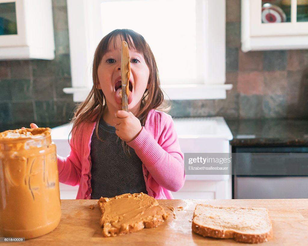 Girl making a peanut butter sandwich, licking the knife : Stock Photo