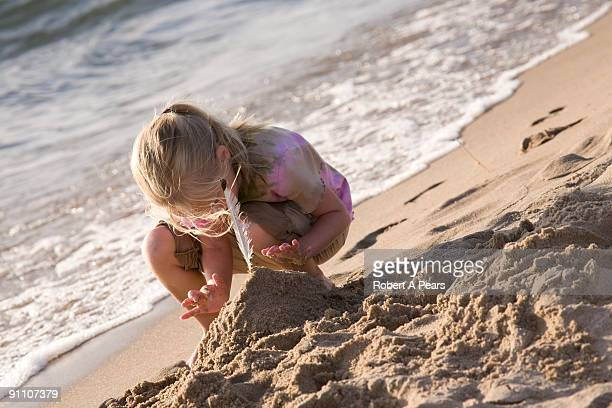 Girl making a sand castle on the beach