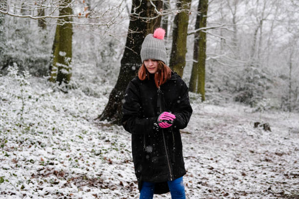 Girl Making A Snowball In The Woods