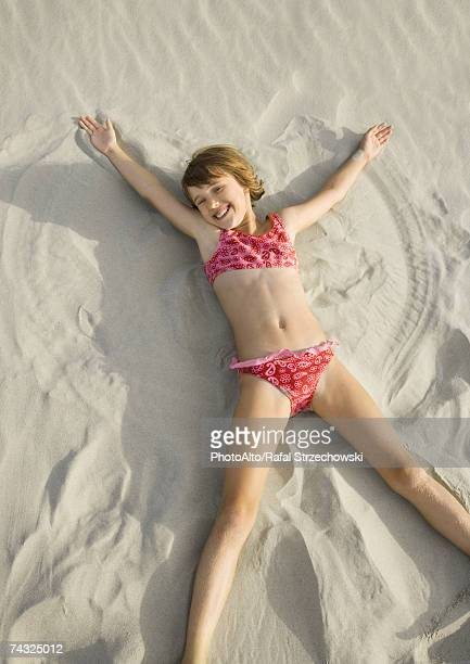 girl making angel in sand on beach, high angle view - legs apart stock photos and pictures