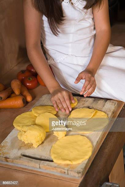 Girl making arepas from masa