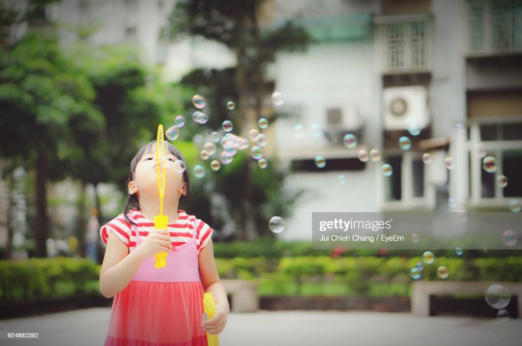 Girl Making Bubbles From Wand In Back Yard : Stock Photo