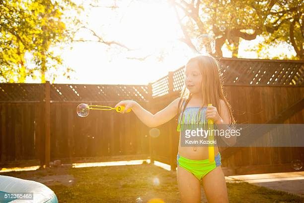 Girl making bubbles with bubble wand in garden
