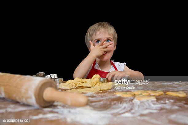 Girl (2-3 years) making cookies and licking fingers