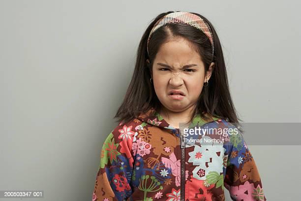 Girl (8-10) making face, portrait