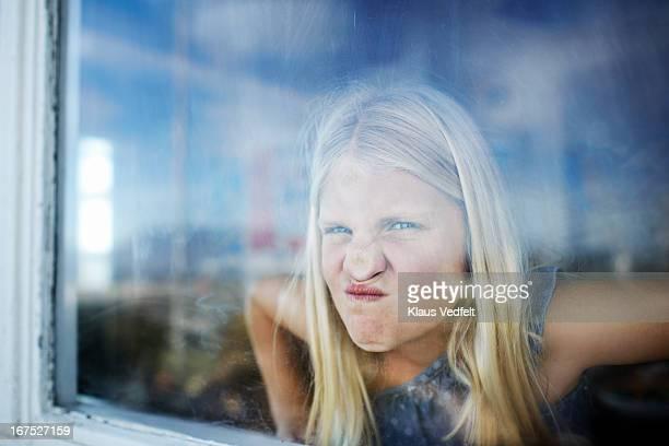 girl making funny face behind window - respektlosigkeit stock-fotos und bilder