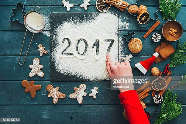 Girl making gingerbread men cookies and writing 2017 in icing sugar