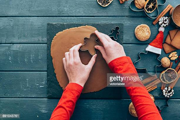 Girl making gingerbread men cookies