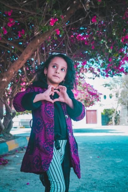 Girl Making Heart Shape While Standing Against Tree