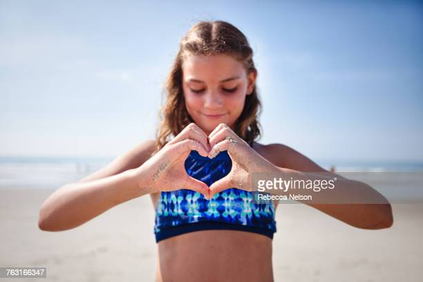 Girl making heart shape with hands on beach