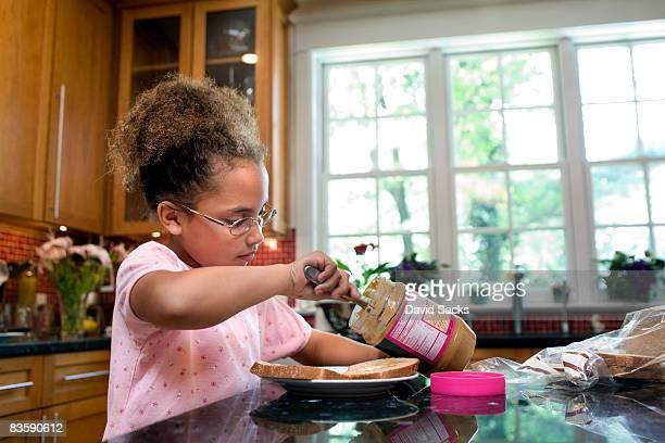 Girl making herself peanut butter sandwich