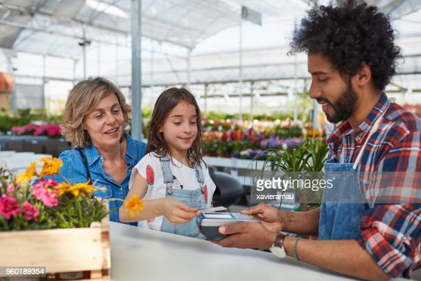 girl making nfc payment with card to gardener - family with one child stock pictures, royalty-free photos & images