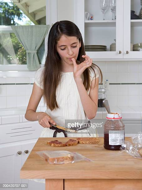 Girl (10-12) making peanut butter and jelly sandwich in kitchen