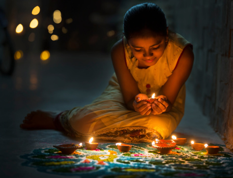 Girl making Rangoli and decorating with Oil lamps for Diwali 454353339
