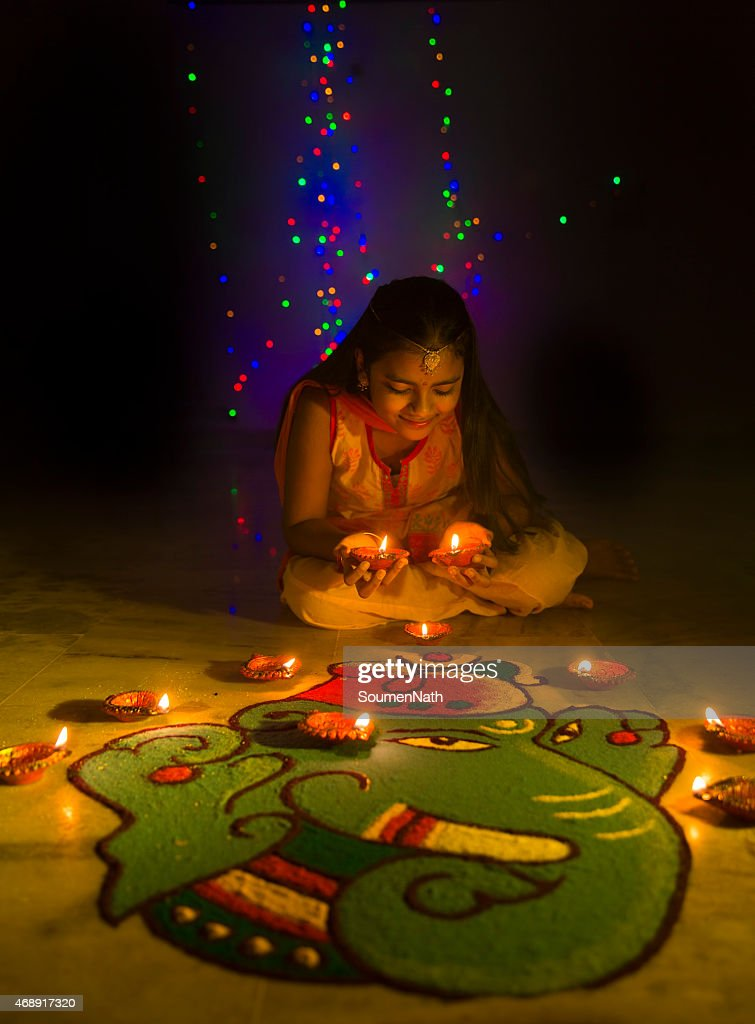 Girl making Rangoli and decorating with oil lamps for Diwali : Stock Photo
