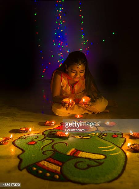 girl making rangoli and decorating with oil lamps for diwali - diwali celebration stock photos and pictures