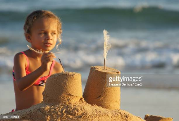 Girl Making Sandcastle At Beach During Sunset