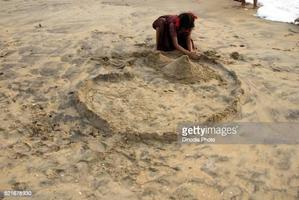 Girl making sandy home on sand at cherai beach, Cochin, Kerala, India