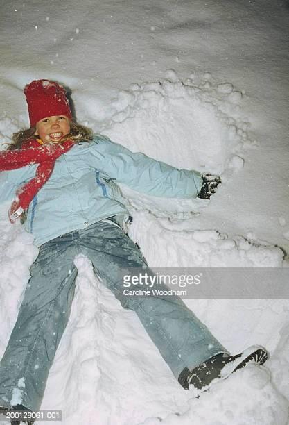 Girl (8-10) making snow angel, portrait