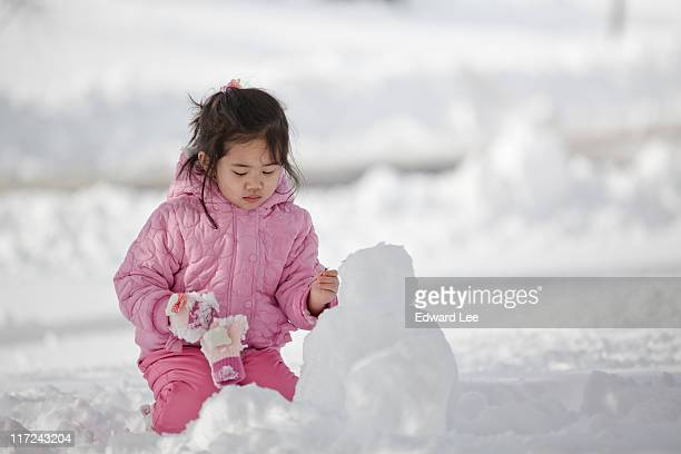 girl making snowman - germantown maryland stock photos and pictures