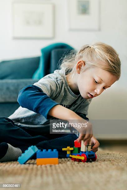 Girl making toy car with blocks while sitting on floor at home