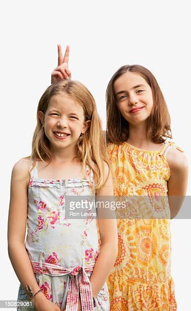 Girl making 'V' sign over friend's head, portrait