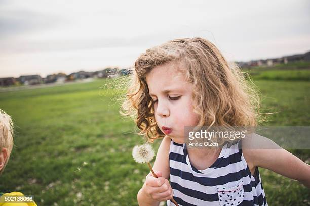 Girl Making Wishes on Dandelion While Brother Stands Next to Her