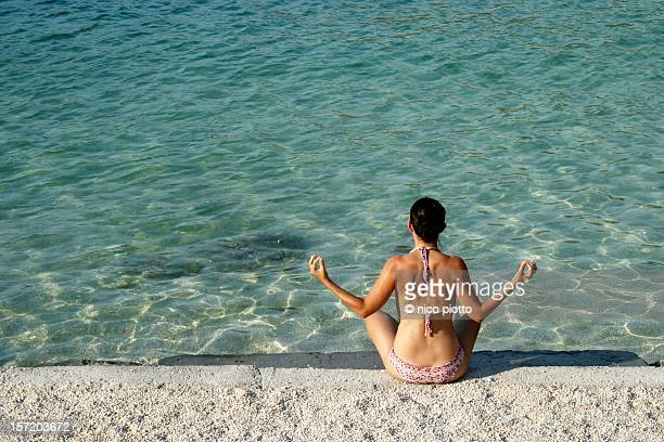Girl making yoga in front of sea