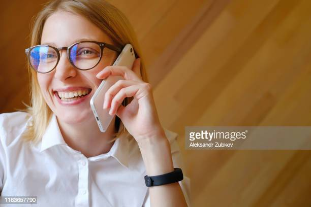 girl manager, freelancer, business lady with glasses in the interior of the house, office, cafe or coworking. talking, talking on a mobile phone, smiling. - caf photos et images de collection