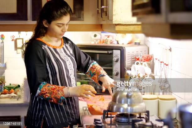 a girl marinating meat in a bowl in her domestic kitchen. - pakistan stock pictures, royalty-free photos & images