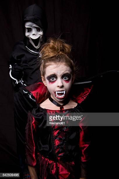 Girl masquarade as vampire and boy wearing Scream mask