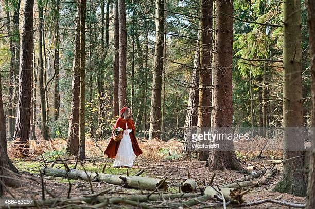 girl masquerade as red riding hood on the move in the wood - le petit chaperon rouge photos et images de collection