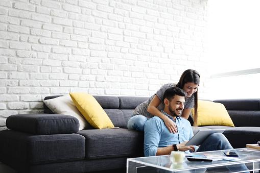 Girl Massaging Boyfriend On Sofa At Home 1012879246