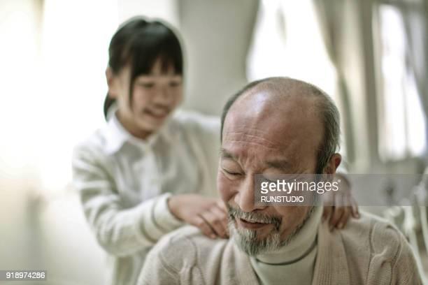 girl massaging grandfather