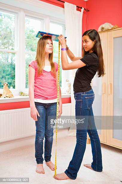Girl measuring friend's (12-13) height with tape measure