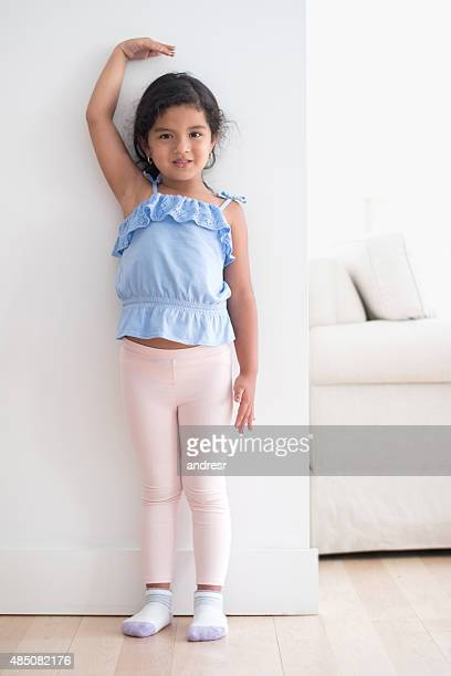 Girl measuring her height against the wall