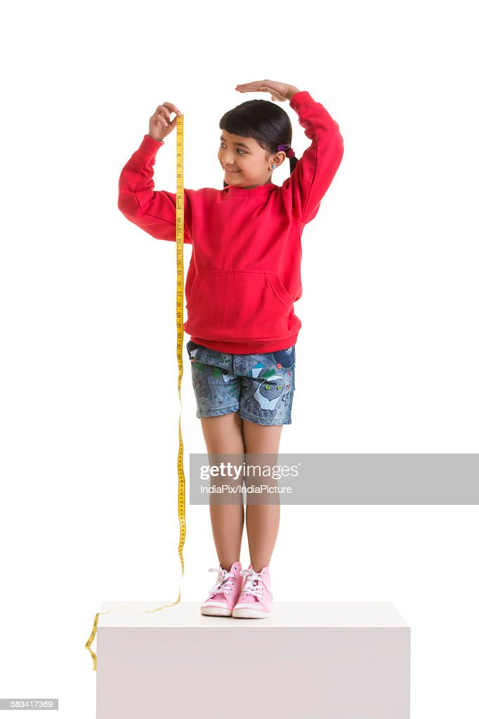 Girl measuring her height : Stock Photo