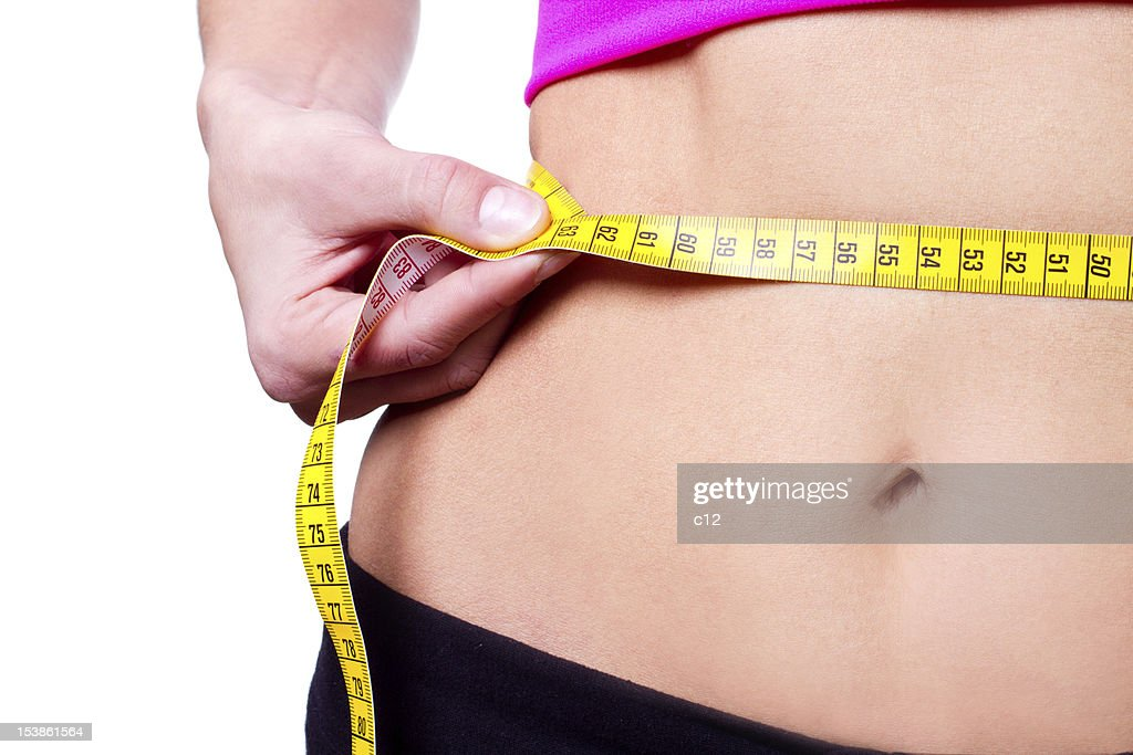 A girl measuring her waistline with a yellow measuring tape : Stock Photo