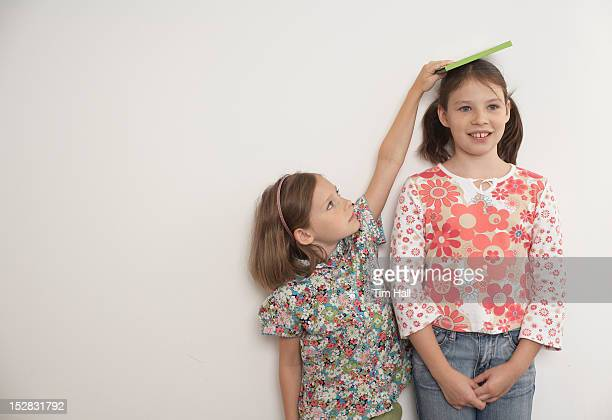 Girl measuring taller sister