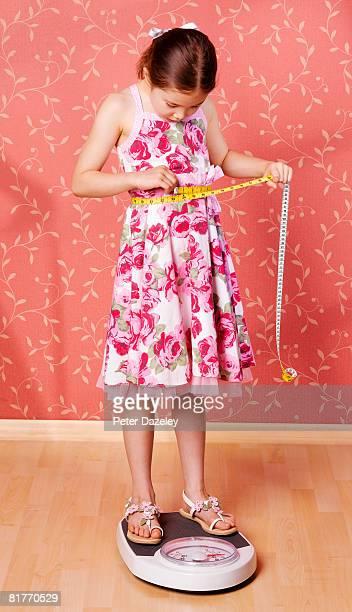 Girl measuring waist on bathroom scales.