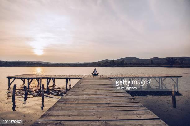 flicka som mediterar vid sjön - chakra bildbanksfoton och bilder
