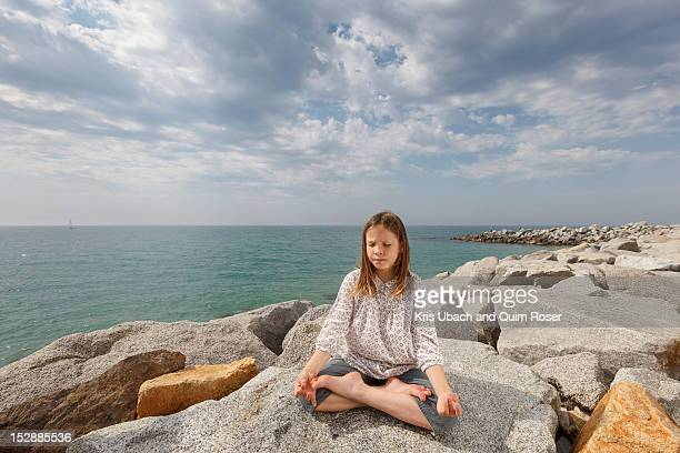Girl meditating on rocks at beach